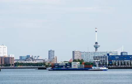euromast: containership entering rotterdam harbor and skyline as background Editorial