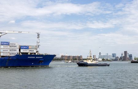 euromast: containership entering rotterdam harbor with tug and skyline as background Editorial