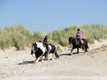free riding: HELLEVOETSLUIS, Paesi Bassi - 27 agosto: Due ragazze a cavallo a cavallo sulla spiaggia di, giugno 28,2014 in Hellevoetsluis, questa spiaggia � una spiaggia free riding per i cavalli