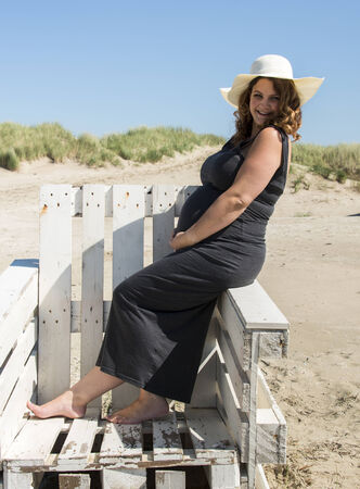 adult happy pregnant woman holding her hands on her belly on the beach with sand and sea photo