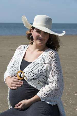 pregnant woman with hat sitting on  the beach with the sea as background photo