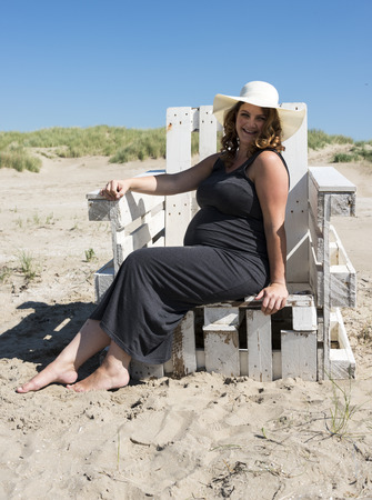adult happy pregnant woman sitting on wooden chair on the beach photo