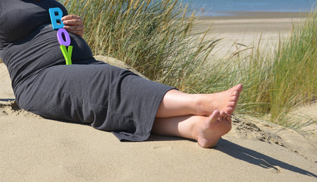 adult pregnant woman holding her hands on her belly on the beach with sand and sea photo