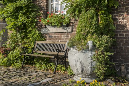old farm with green plants on the wall and seat and vase with plants on the old rocks in the garden photo