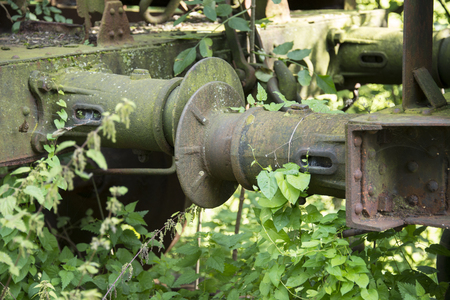 iron old rusted train buffer with green plants overgrown