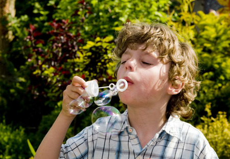 causcasian boy blowing bubbles Stock Photo