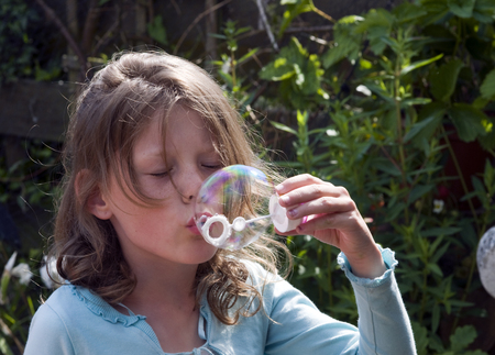 girl blowing: blond causcasian girl blowing soap bubbles