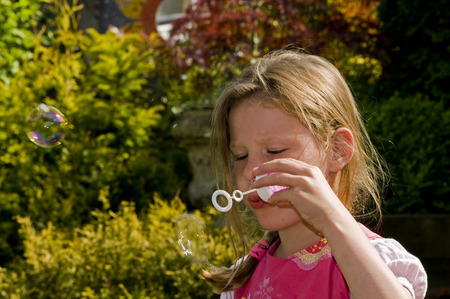 blond causcasian girl blowing soap bubbles
