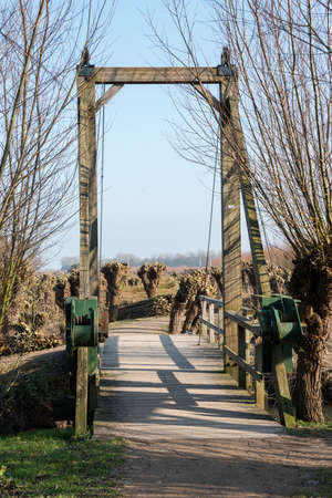 drawbridge: nature area in  holland with willows and  wooden drawbridge and small river