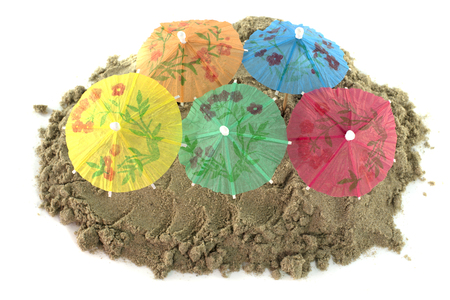 mound: green blue red and green cocktail Umbrellas in Sand Mound