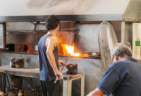 blowers: MDINA,MALTA-SEPTEMBERT 29, 2011: Glass blower making glass in hot fire ,on September 29 2011, the glass blowers are showng their profession to tourist and sell the product when finished