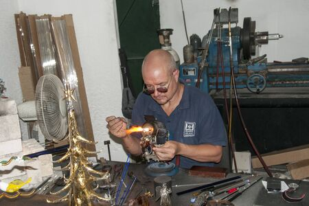 blowers: MDINA,MALTA-SEPTEMBER 29, 2011: Glass blower making glass in hot fire ,on September 29 2011, the glass blowers are showng their profession to tourist and sell the product when finished