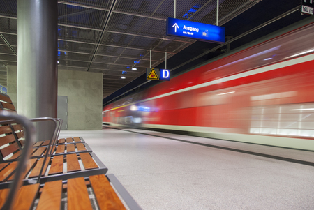 wood pillars: high speed red train crossing trainstation in Berlin Germany Editorial