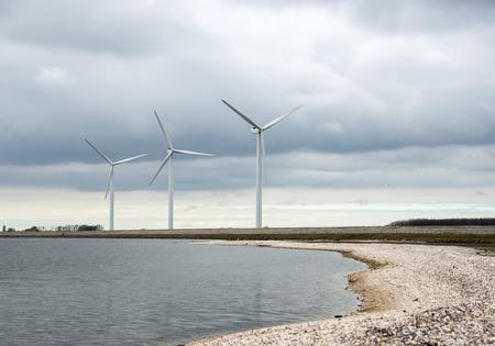 molino: tres molinos de viento en Holanda cerca de un lago de agua