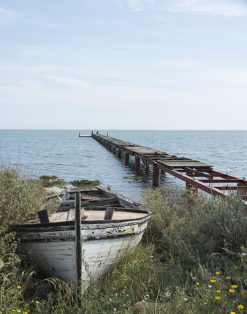ocea: old wooden abandoned boat with rosted iron quay