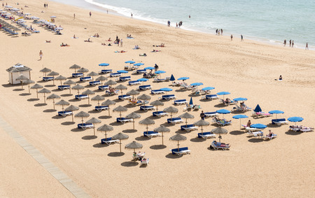 region of algarve: ALBUFEIRA, PORTUGAL - APRIL 23: View of crowded Falesia beach at the midday in the summer mediterranean resort Albufeira on April 23, 2015. This town is a part of famous tourist region Algarve.