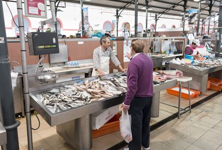 fish selling: LOULE, PORTUGAL - APRIL 4: Man selling fish in the traditional portuguese market in Loulele on  April 4th 2015 in Loule, Algarve, Portugal, this market is the biggest market hall of the algarve Editorial