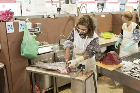 fish selling: LOULE, PORTUGAL - APRIL 4: Woman cleaning the big salmon  fish for selling in the traditional portuguese market in Loulele on  April 4th 2015 in Loule, Algarve, Portugal, this market is the biggest market hall of the algarve