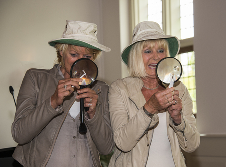 HELLEVOETSLUIS,HOLLAND-JUNE 13,2015:Two woman with magnifying glass busy with investigation in the city hall on June 13, Hellevoetsluis,in this place was found a lot of old material from second world war