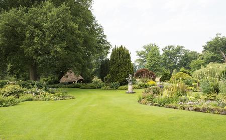 landscaped garden: big green gardenwith ngreen grass flowers and gardenhouse