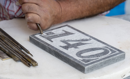 hands work: stonecutter making art from raw stone