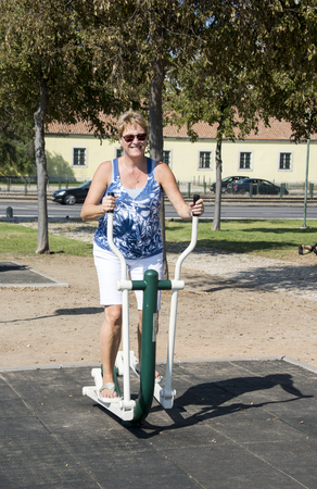 crosstrainer: adult woman with sunglaeese training on outside crosstrainer in the park in lisbon portugal