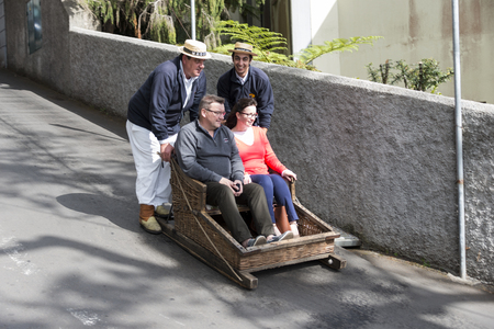 toboggan: FUNCHAL,PORTUGAL-MARCH 19 Toboggan riders  dive with sledge with tourists on MArch 19, 2016 in Monte- Funchal, Portugal. This is done on public streets and is an old tradition only of this island
