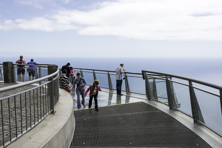 straight up: FUNCHAL,PORTUGAL-MARCH 25, Unidentified people looking to the ocean from the Miradouro do cabo Girao on Madeira island on March 25 2016 in Funchal, this viewpoint is 550 meters straight up from sea level Editorial