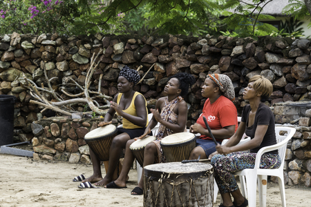 way of living: HOESPRUIT,SOUTH AFRICA- MAR 9, 2014: Unidentified african woman playing the drum s for the tourists on march 9 2014 in Hoedspruit,this is the only way of making a living for the woman from the townships Editorial