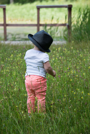 18 month old: AMSTERDAM,NETHERLANDS- JULI 9, 2016: Unidentified little girl 18 month old with red hair wlaking in green grass wairing a hat on Juli 9 2016 in Amsterdam,Girls with red hair are becoming less Stock Photo