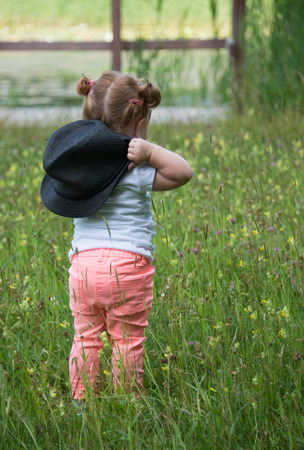 18 month old: Unidentified little girl 18 month old with red hair wlaking in green grass wairing a hat on Juli 9 2016 in Amsterdam,Girls with red hair are becoming less
