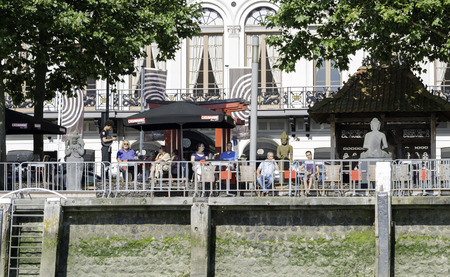 maas: ROTTERDAM,NETHERLANDS- AUGUST 31, 2016: Unidentified people sitting on waterfront terrace looking over the river Maas on August 31 2016 in Rotterdam,this is the biggest port in Holland and also one of the biggest in the world Editorial