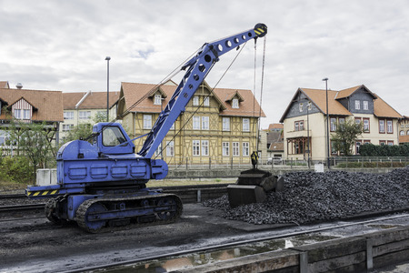 wood railroad: old blue crane with crawler with bucket to load coal into the steam locomotive
