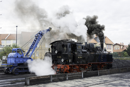 brocken: WERNIGERODE,GERMANY, SEPTEMBER 21,2016: Unidentified crane driver loading coal in steam locomotive in Wernigerode on september 21 2016,The trains to the Brocken mountain operate around the year for tourists.