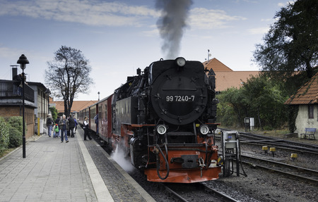 brocken: WERNIGERODE,GERMANY, SEPTEMBER 21,2016: Unidentified people entering the steam train for a drive to the mountain in Wernigerode on september 21 2016,The trains to the Brocken mountain operate around the year for tourists.