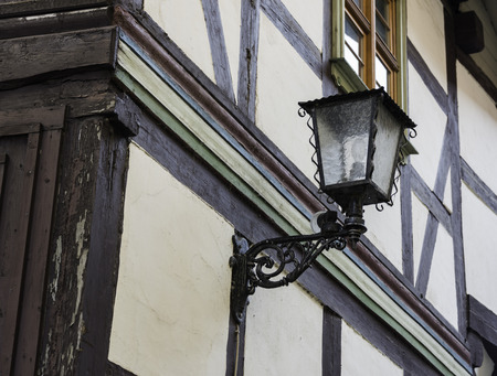 half timbered house: old vintage antique lamp at half timbered house typical for germany with white plaster and wooden beams Stock Photo