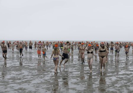 traditon: ROCKANJE,NETHERLANDS - JANUARI 1 2017 :Unidentified people running into the sea for the new years dive in Rockanje on Januari 01, 2017. New years dive is a traditon  to start the new year
