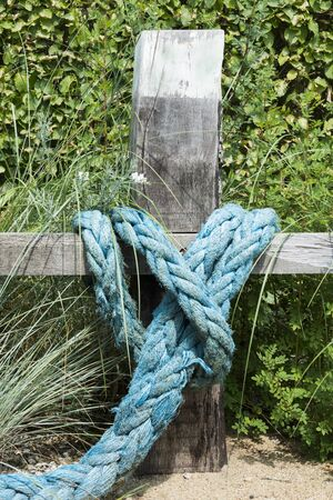 blue rope knotted wooden pole in garden