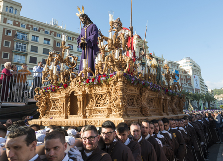 seville: MALAGA,SPAIN-APRIL 09 2017:Unidentified people walking in the catholic processions called Semena Santa in Malaga on April 09 2017, this processions are every year the sunday before easter Editorial