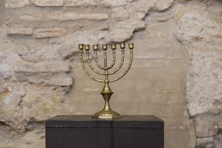 old religious menorah with ancient wall