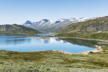 walking track in national park from bitihorn to stavtjedtet with lakes fjord and snow on the mountains
