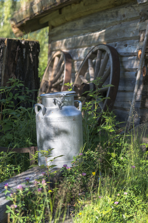 old milk churn in natural environment in fron of old wooden house in norway