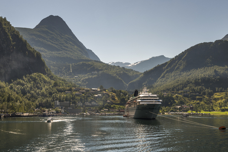 cruise ship on geirangerfjord in norway with snow on the hills in summer Stock Photo