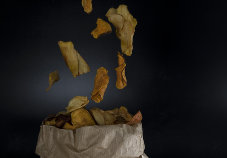 healthy vegetable chips falling in a paper bag