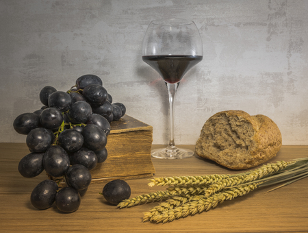 A wheat bread and shock of wheat with red grapes and glas of red wine and bible as easter background