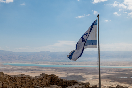 the israelian flag with the dead sea as background, seen from masada