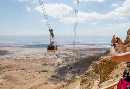 woman making photo of the cable car going to masada in israel