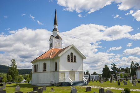 white wooden stave church near Leira in Norway with cemetery