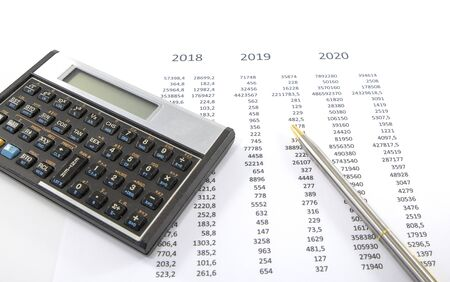 calculating the finance situation for 2020 wit paper pen and calculator
