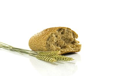 A wheat bread and shock of wheat on a white background